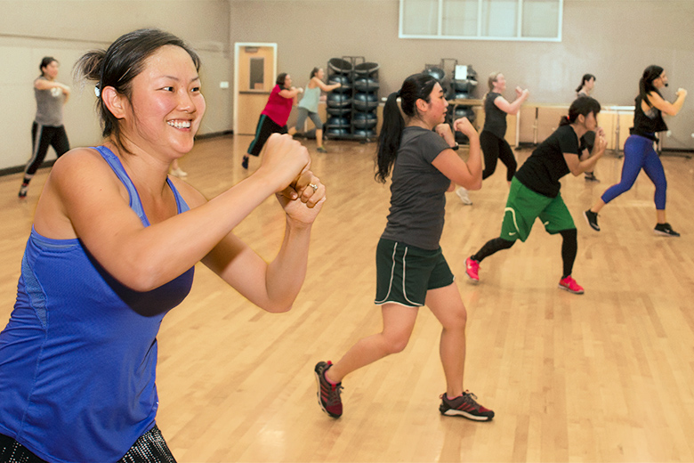 An instructor leads a kick boxing class.