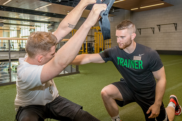 A personal trainer works with a student in the Fitness Yard.