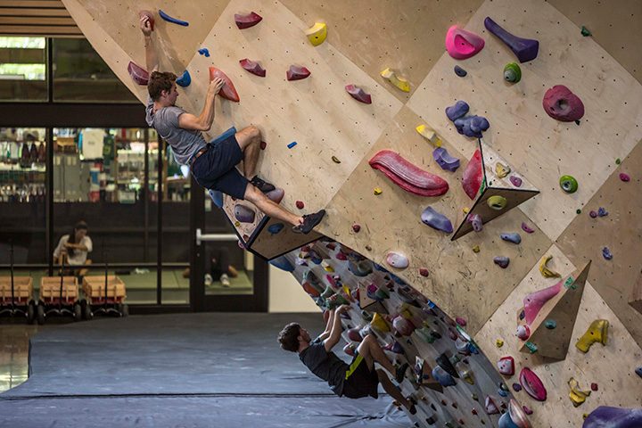Two people work their way up the bouldering wall.
