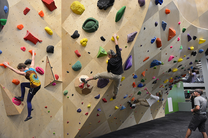 Four climbers navigating routes on the bouldering wall.