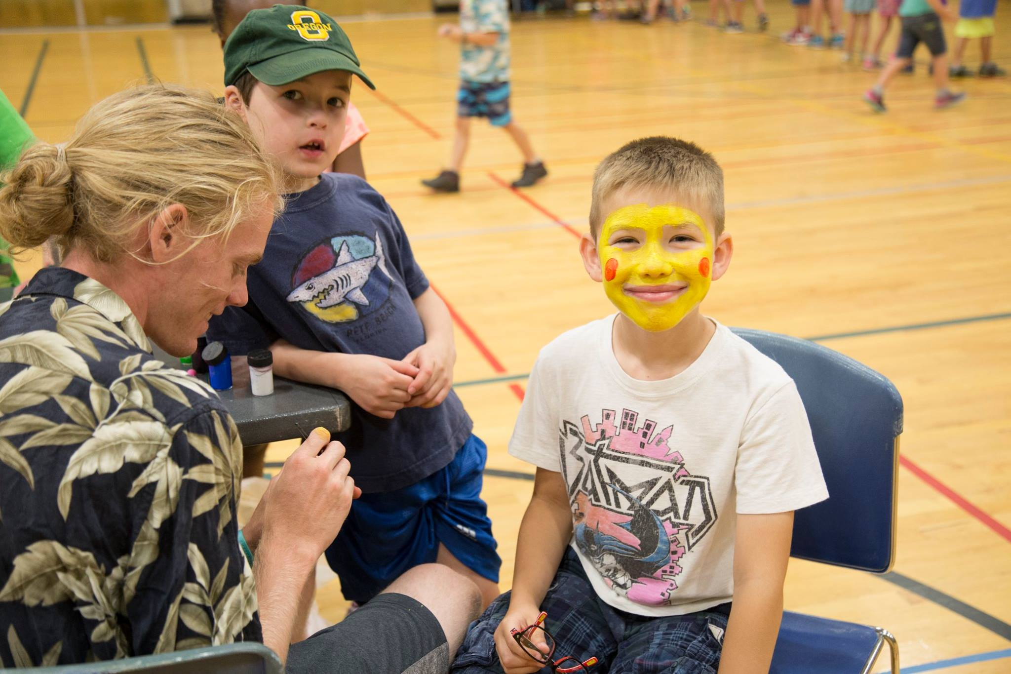 Two children get their faces painted.