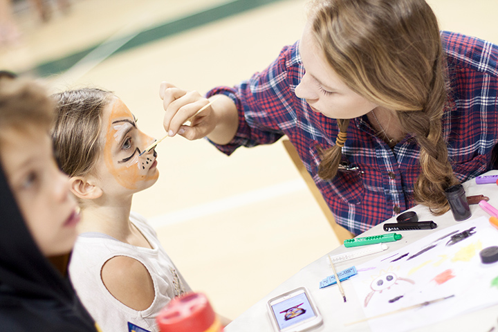 A counselor paints a girl's face like a cat.