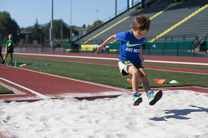 A young boy jumps into the long jump pit on Hayward Field.