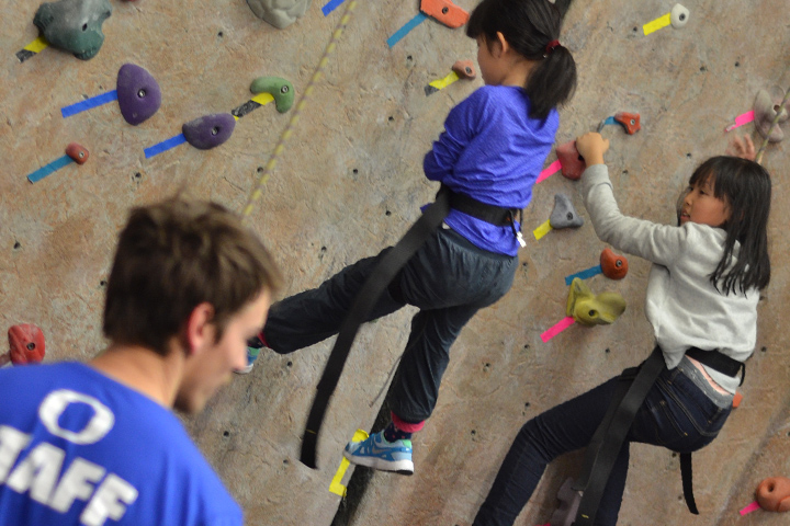 Two girls climb on a walk wall under the guidance of an instructor on the floor.