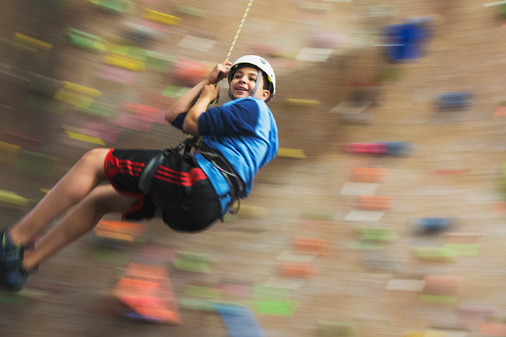 A young teen swings on a rope on the rock wall.