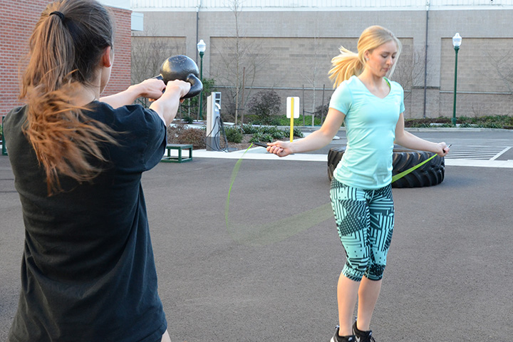 One girl jumping rope while another girl swings a kettle bell in the Fitness Yard.