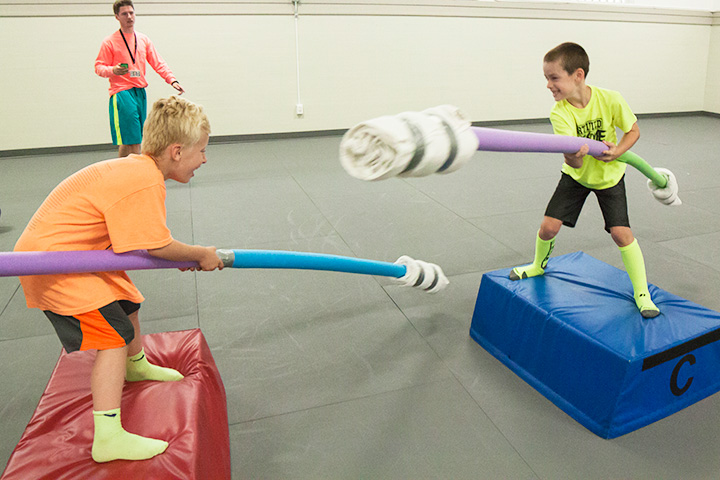 Two boys try to knock each other off their platforms with pool noodles.