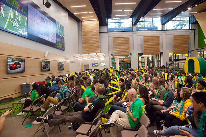 Lounge full of people sitting and watching a Ducks footbal game on the big screens.