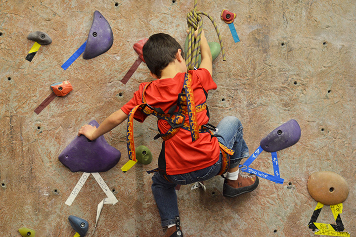 A boy climbs the rock wall.