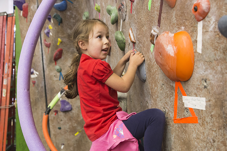 A young girl climbs on the bouldering wall.