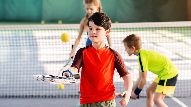 A young boy practices hitting the ball with his tennis racquet while other kids practice behing him.