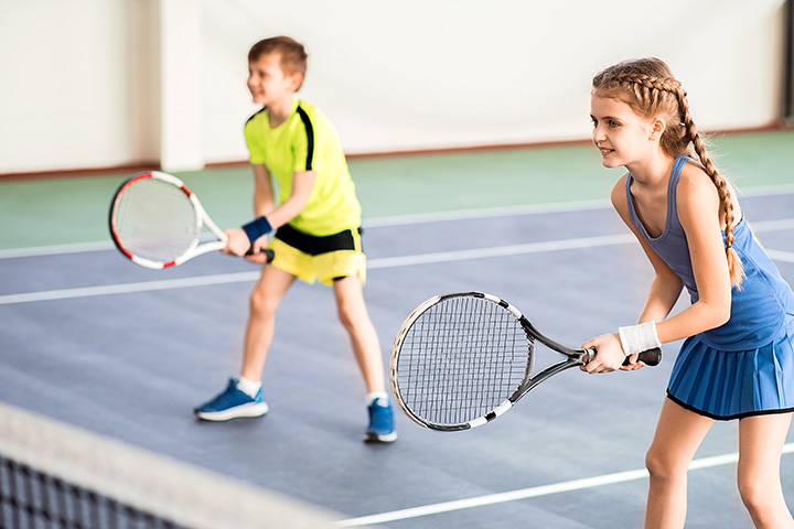 Two kids stand in the ready position with their tennis racquets waiting for the tennis ball to come their way.