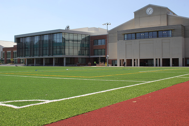 Wide view of empty turf field with the Rec Center in the background.